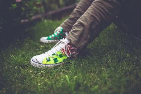 Gros plan sur les souliers d'une personne assise dans l'herbe.