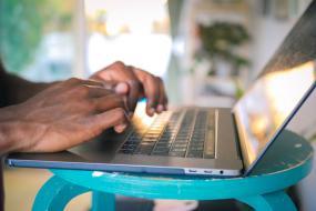 Photographie en gros plan des mains d'une personne qui tappe au clavier d'un ordinateur portable.