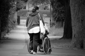 Photographie en noir et blanc d'une personne poussant une personne en fauteuil roulant.