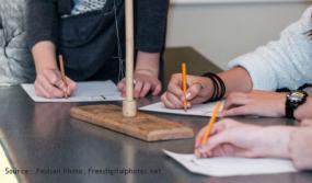 Vu sur les mains des trois personnes écrivant sur une table.
