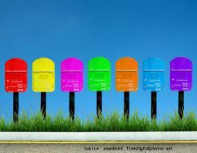 Photographie d'une rangée des boîtes aux lettres colorées sur le bord d'une route.