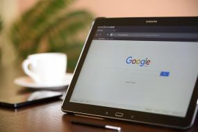 Photographie d'une tablette électronique posée sur une table. On voit à gauche en arrière-plan, un téléphone cellulaire et une tasse de café.