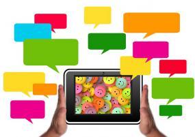 Des mains tiennent une tablette où l'écran est remplie de bonhommes sourire colorés. Plusieurs phylactères entourent la tablette.