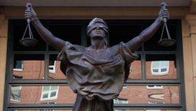 Photographie d'une statue de la justice qui se trouve devant des fenêtres.