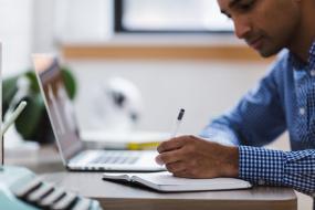 Une personne écrit sur une table, un ordinateur portable est placé à sa gauche.