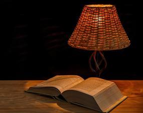un livre ouvert et une lampe sur une table