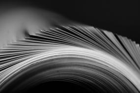 Photographie en gros plan et en noir et blanc des pages courbées d'un livre ouvert.