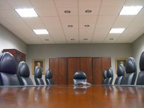 Photographie d'une salle de conférence vide. L'angle de la caméra est au niveau de la table.