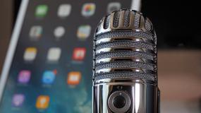 Un vieux microphone avec une tablette électronique en arrière-plan.