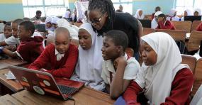 Des enfants regardent un ordinateur portable dans une salle de classe bondée.