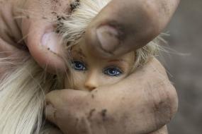 Photographie d'une main sale qui tient une tête de poupée Barbie.