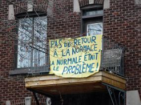 Accrochée à la balustrade d'un balcon d'appartement, un banderole où il est écrit « Pas de retour à la normale, la normale était le problème! ».
