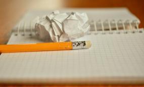 Photographie d'un cahier ouvert avec un crayon et une boulette de papier posés dessus.