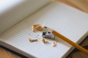 Sur un cahier ouvert, un crayon y est déposé à coté d'un aiguise crayon et de retailles de crayons.