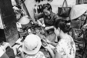 Photographie en noir et blancs de personnes qui travaillent  à réparer des chaussures dans un atelier exigu.