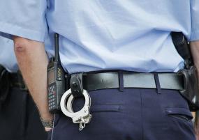 Photographie en gros plan, cadré sur les hanches, d'un policier. Des menottes pendent de sa ceinture.