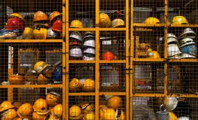 Photographie de tablettes grillagées jaunes contenant plusieurs casques de sécurité.