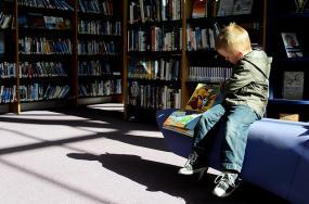 Un enfant lit un livre sur un fauteuil dans bibliothèque.