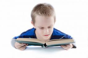 Un enfant vue de face qui lit un livre.