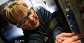 Photographie en gros plan d'une électricienne au travail.