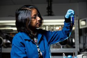 Photographie d'une scientifique en sarrau bleu qui tient une éprouvette.