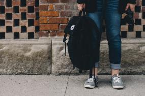 Une personnes tient un sac à dos dans sa main droite. Prise de vue en bas de la taille, sur un mur de brique.