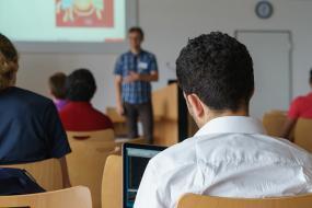 Photographie d'une salle de classe de la perspective d'une personne assise à l'arrière.