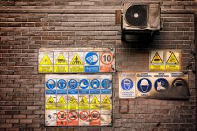 Un mur de brique avec des affiches de sécurité.