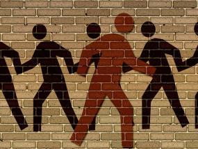 Illustration sur un mur de brique de pictogrammes noirs représentant des personnes allant dans le même sens. En avant-plan, un pictogramme orange représentant une personne se dirige dans le sens opposé.
