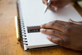 Plan rapproché de mains qui tracent des lignes dans un cahier à l'aide d'une règle.