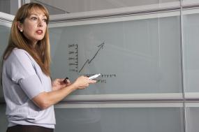 Une personne se tient à côté d'un tableau où un graphique est dessiné.