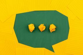 Photographie de Post-its jaunes qui forme un phalanstère sur un fond vert. Trois Post-its chiffonnés sont placés au milieu.