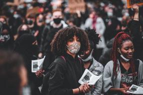 Photographie d'un groupe de femmes noires portant des masques à une manifestation. Elles tiennent des tracts.