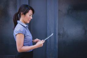 Photographie d'une femme qui se promène pendant qu'elle regarde une tablette électronique.