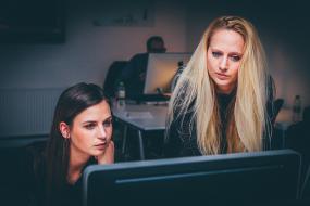 deux femmes regardent un écran d'ordinateur, l'une assise et l'autre debout