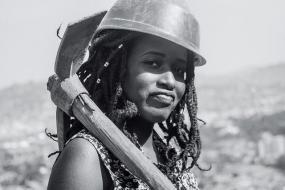Photographie en noir et blanc d'une travailleuse tenant un pic sur son épaule.