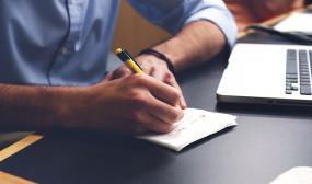 une personne écrit sur une table, un ordinateur portable est placé à sa gauche